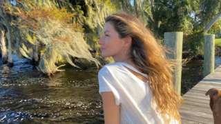 A modelo Gisele Bündchen está sentada em um píer contemplando a paisagem