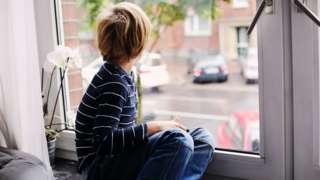 child sitting alone at window