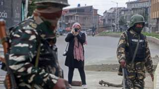 Photojournalist Masrat Zahra (Rear) takes photos near a temporary checkpoint before going to Cyber Police Station in Srinagar, Kashmir