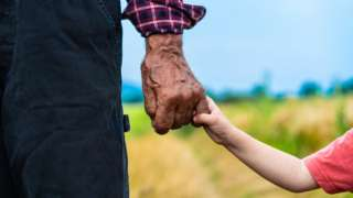 Old man holding young child's hand