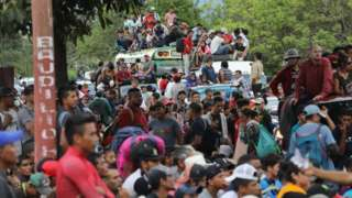 Dozens of migrants are pictured waiting