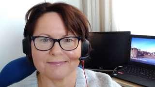 Bridget Thomas wearing a headset at her desk