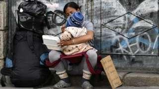 Một bà mẹ Venezuela di cư đang xin ăn trên đường phố La Paz on 10/122019