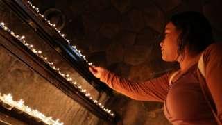 आबु धाबीस्थित सेन्ट जोसेफ्स कथिड्रल क्याथोलिक चर्चमा मैनबत्ती बाल्दै एक महिला