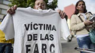"""A woman holds a T-shirt reading """"Victim of the FARC"""" during a protest in Bogota on 13 July 13 2018"""