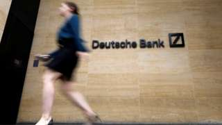 Pedestrian walk past the offices of of German bank Deutsche Bank in central London on July 8, 2019.