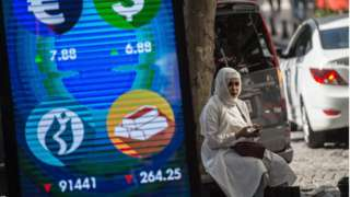 A woman sits beside a digital billboard giving market updates in Istanbul in August 2018