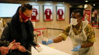 A member of the Royal Artillery hands a test to people at a testing centre at Liverpool Football Club's Anfield stadium