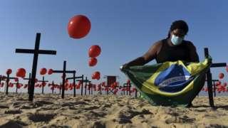 A man holds Brazilian flag between red balloons in Rio de Janeiro
