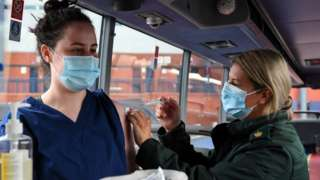 Cheryl Barr of the Scottish Ambulance Service, gives Fiona Douglas, 26, a vet from Falkirk, an injection of a Covid-19 vaccine on the Scottish Ambulance Service vaccine bus in Glasgow
