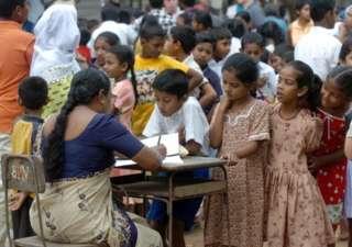 A Sri Lankan school teacher registers school children at the Sudarma Ram school in the southwestern coastal town of Magalle 10 January 2005