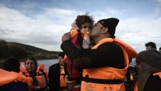 A man kisses a girls as refugees and migrants arrive on the Greek island of Lesbos in December 2015