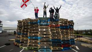 Loyalists standing on the bonfire at Avoniel Leisure Centre