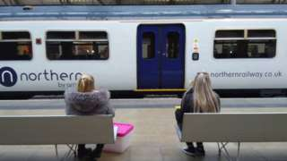 women sit on platform looking at northern railway train