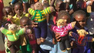 Children in Africa with knitted teddies