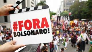 A demonstrator holds a sign that says 'Bolsonaro out'