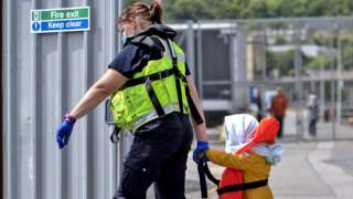 A young child is led to an intake facility after arriving in Kent