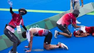 """Switzerland""""s Max Studer and Jonathan Brownlee of Britain are exhausted in the finish area during the men""""s Individual Triathlon competition at the 2020 Tokyo Summer Olympics in Tokyo"""