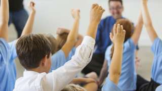 Pupils in classroom with hands up