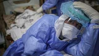 عامل صحي ينتظر بالقرب من مريض كوفيد -19، في إدلب، سوريا في 23 فبراير/شباط 2021
