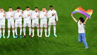 A person waving the rainbow flag runs on the pitch as the Hungary players line up for the national anthems the UEFA EURO 2020 Group F football match between Germany and Hungary at the Allianz Arena in Munich on June 23, 2021