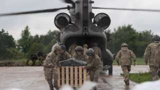 Crews loading the Chinook helicopter