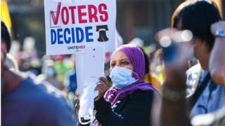 """A protester holds a sign reading """"voters decide"""" during an eleciton rally in Philadelphia"""