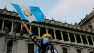 A woman holds up a Guatemalan flag, during a protest to demand the resignation of President Alejandro Giammattei on November 22, 2020.