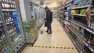 Shopper with lines on floor to mark social distancing in a supermarket