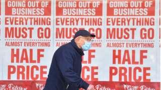 Man walks past shop closure sign