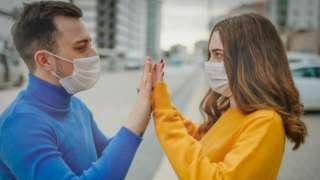 فتاة وشاب يرتديان أقنعة طبية