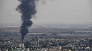 Smoke rises over the Syrian border town of Ras al-Ain on Friday 18 October, despite Turkey halting its operation