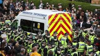 People surrounding immigration van