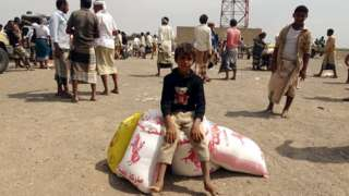 Displaced Yemenis receive food aid donated by a British organisation in Yemen's western province of Hodeida