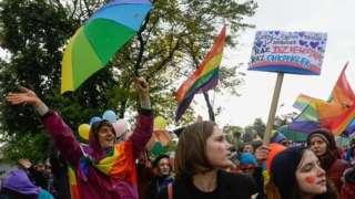 A woman holds a rainbow flag during an Equality/Pride march on October 06, 2019 in Nowy Sacz, Poland