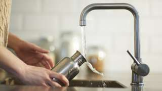 A woman cleans a water bottle in a kitchen sink