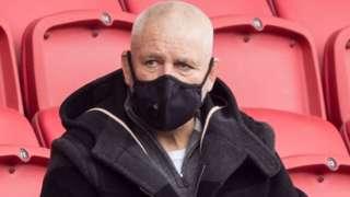 Warren Gatland wears a mask as he watches some Lions contenders