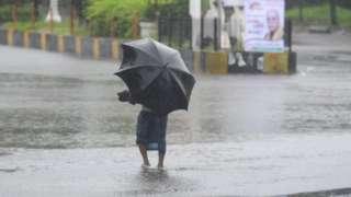 A man with an umbrella wades through floodwater in Khulna, Bangladesh