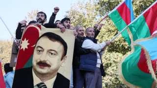 Gente con banderas azerbaiyanas celebrando el fin del conflicto