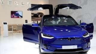 Un auto Tesla con las puertas abiertas.