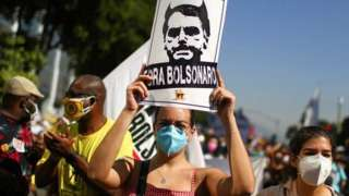 """A person holds a sign reading """"Bolsonaro out"""" during a protest calling for the impeachment of Brazil's President Jair Bolsonaro in Rio de Janeiro, Brazil, on 3 July 2021"""
