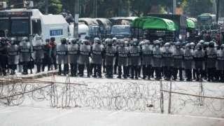 防暴警员手持盾牌,在仰光大学附近的街道上利用铁线网布防