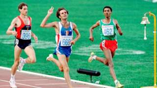 Pascal Thiebaut of France (C), surrounded by Abel Anton Rodrigo of Spain (L) and Fita Bayisa of Ethiopia (R), waves after winning the Men's 5000m semi- final athletics event of the Barcelona Olympic Games, on August 6, 1992 in Barcelona.