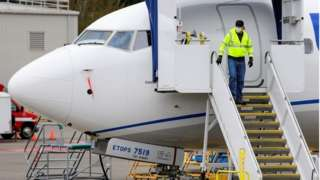 Boeing worker coming down steps of plane in facemask