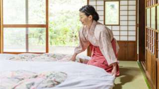 Una mujer oriental prepara un futón.