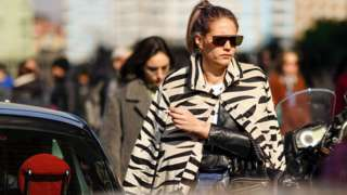 A guest wears earrings, sunglasses, a beige and black zebra pattern jacket, a black leather jacket, outside MSGM, during Milan Fashion Week Fall/Winter 2020-2021 on February 22, 2020