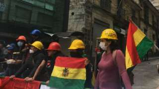 A group of protesters wearing hard hats man a barricade near Mr Morales' home and office