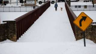 Anna Thomasson walks her dog, Penny, across the White Rock Lake Spillway after winter weather caused electricity blackouts in Dallas, Texas, U.S. February 18, 2021