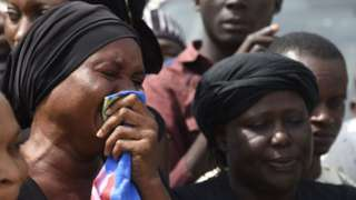 A woman cries as the casket of a relative is brought to Ibrahim Babanginda Square in the Benue State capital Makurdi, on January 11, 2018, during a funeral service for scores who died following clashes between Fulani herdsmen and natives of Guma and Logo districts.