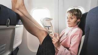 항공기 앞 좌석에 두 발을 올리고 있는 여성